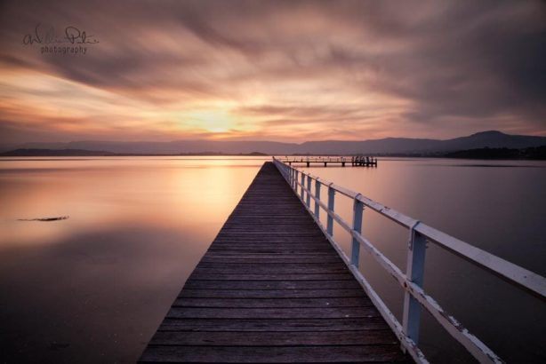 Sunset over lake illawarra with a pier leading into the sun.