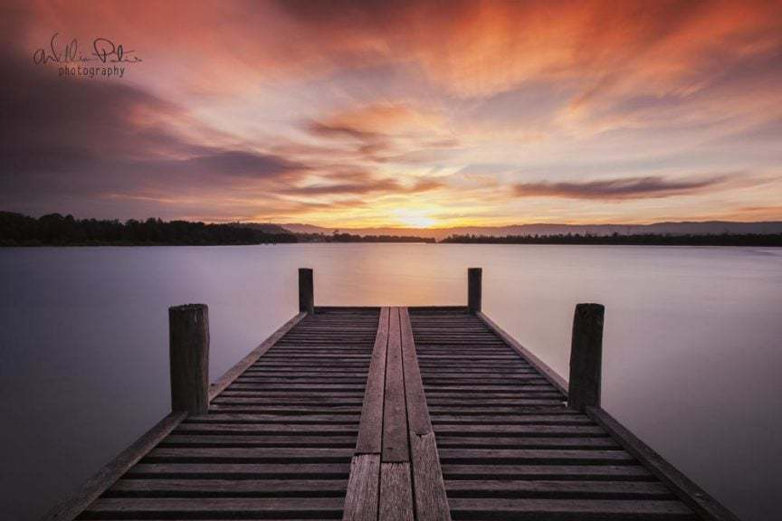 A small pier on a lake with a fiery sunset .