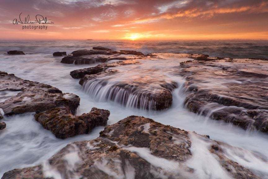 Running water over rocks on the beach at sunrise. Illawarra.