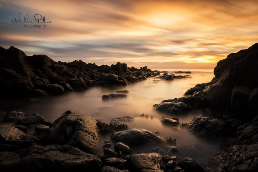 Rugged rocks upon the shore line are illuminated by the rising sun, surrounded by misty water.