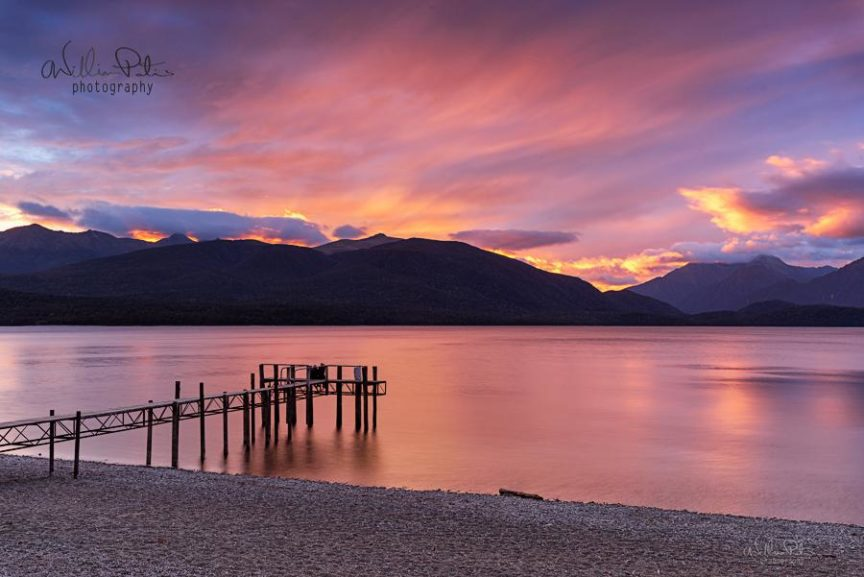 A pier on a lake with a pink sky at sunset.
