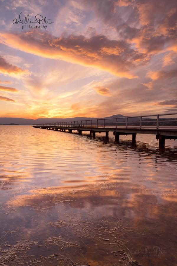 A fiery sunset over a lake with a pier.