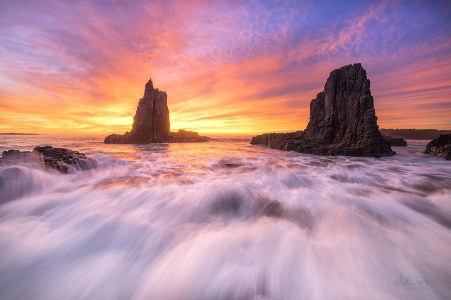 A vibrant sunrise behind sea stacks