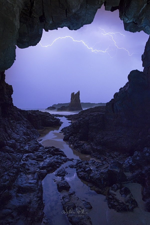 Lightning storm outside a sea cave