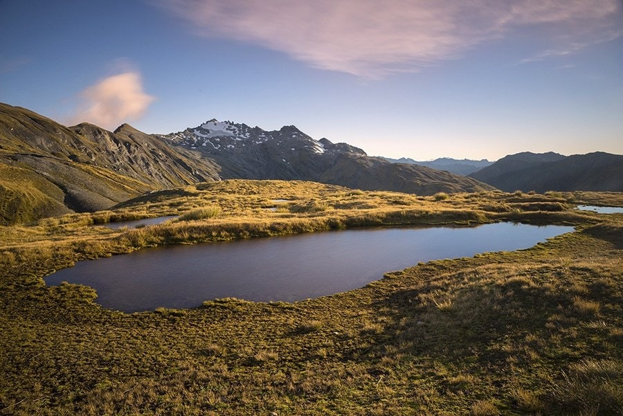 Mountains and a tarn at sunset.