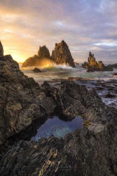 Sunrise over a rocky coast line.