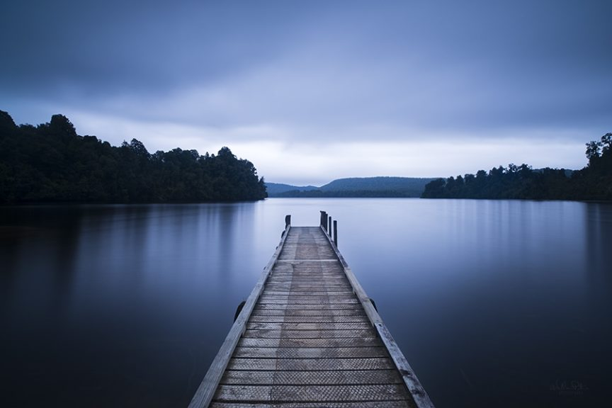 A pier leading out over a lake under gloomy skies.