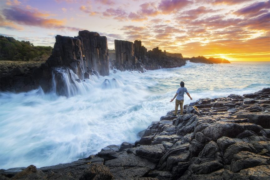A man standing before a raging sea at sunrise.