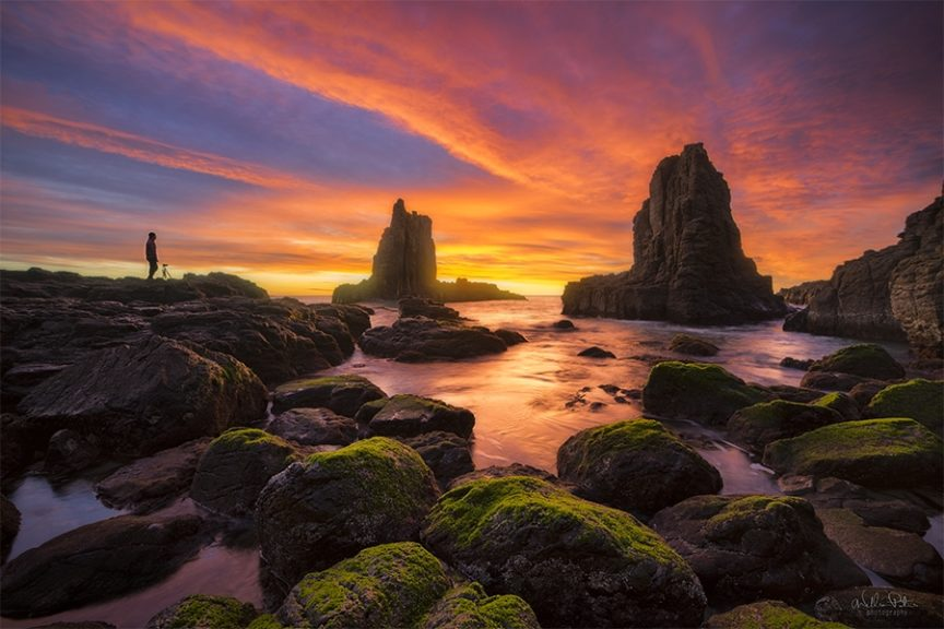 Sea stacks under a vibrant sunrise.