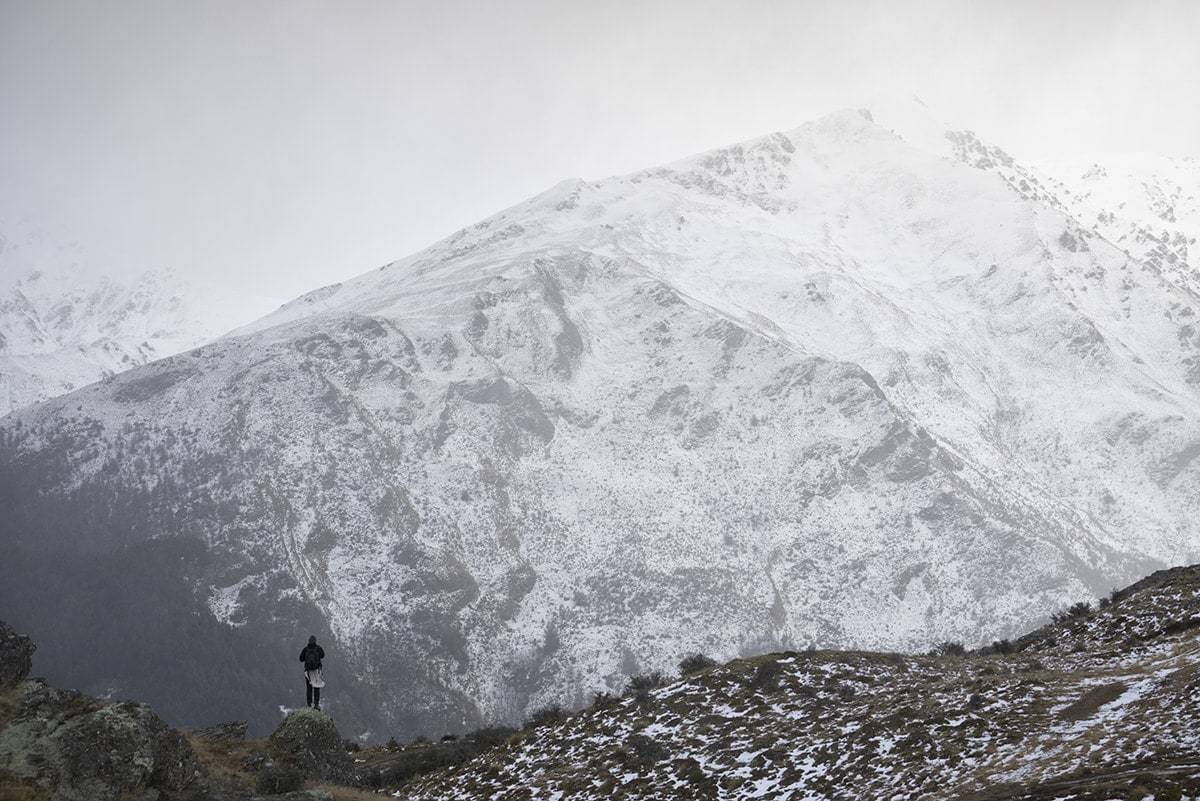 A man standing before snow covered mountains in New Zealand.