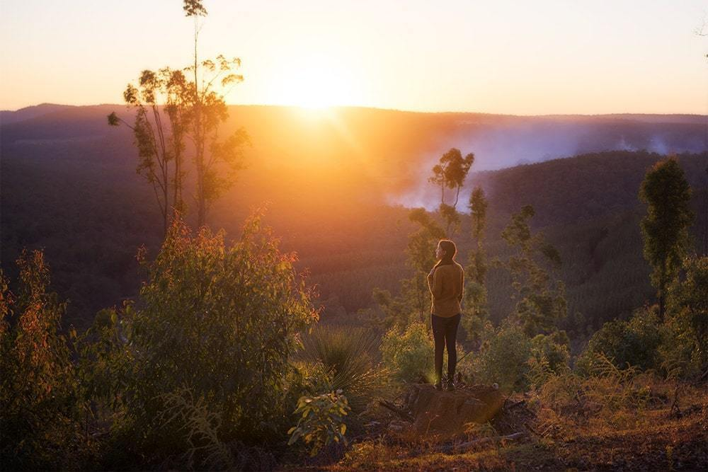 A woman in the wilderness at golden hour.