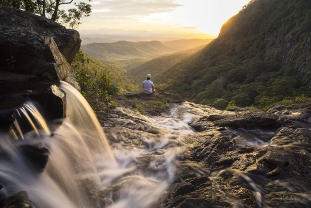 A man sitting by a waterfall at sunset.