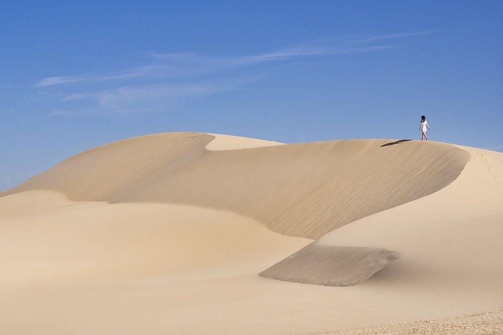 A woman walking along sand dunes.