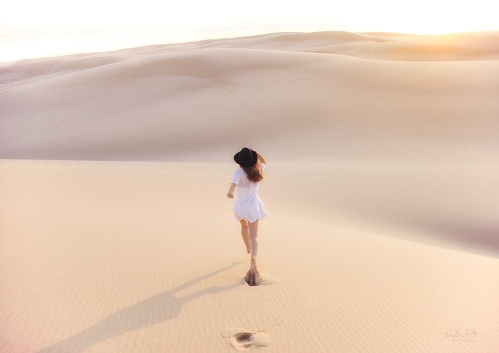 A girl running through golden sand dunes.