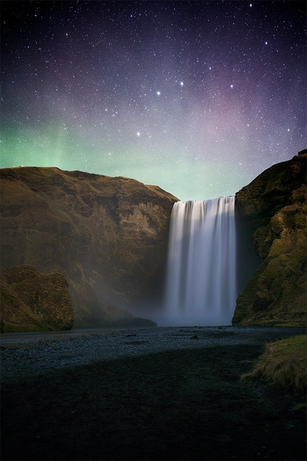 The Northern Lights dancing above a waterfall in Iceland