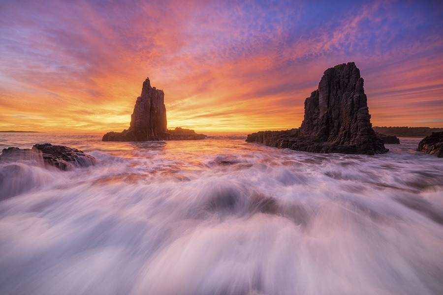 A colorful sunrise over sea stacks