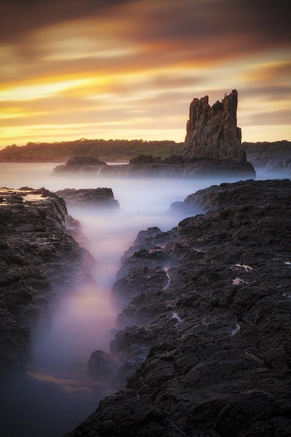 Sunrise by a rock coastal seascape