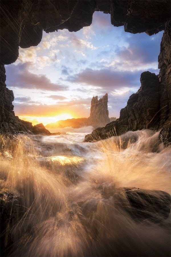 Water rushing inside a sea cave at sunrise