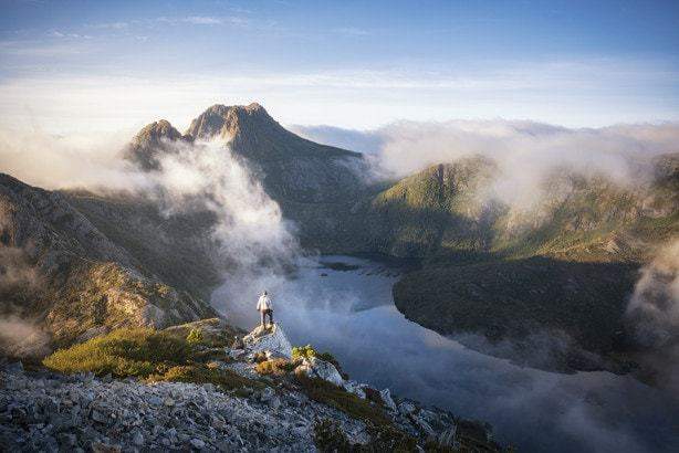 A man standing on a mountains edge above a foggy lake