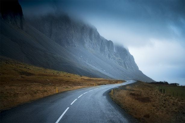 A road leading towards a gloomy mountain