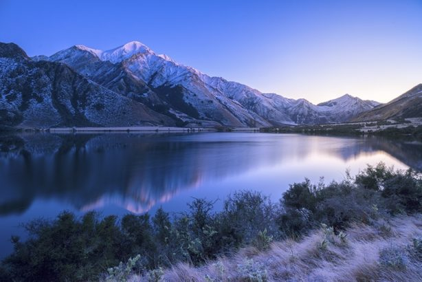 A snow capped mountain reflected in a glassy lake at dawn