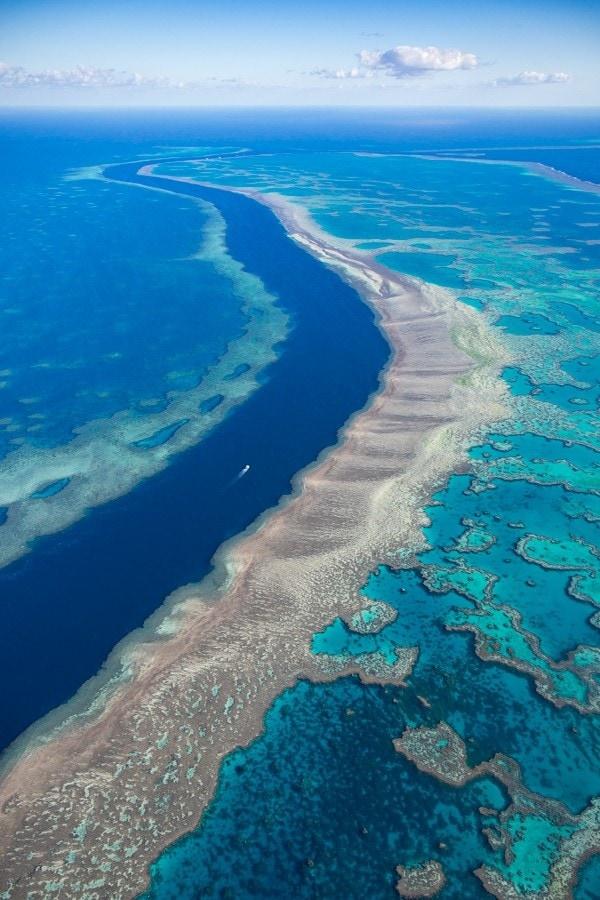 Aerial image of a boat cruising between reefs