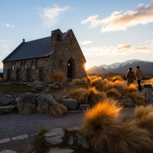A couple walking toward a stone church at sunrise