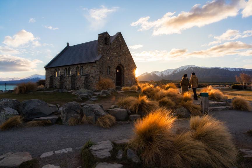 A couple walking toward a stone church at sunrise