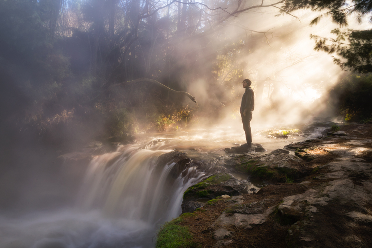 A man standing in fog above a waterfall