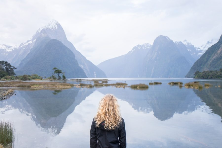A woman standing before mountains and lake