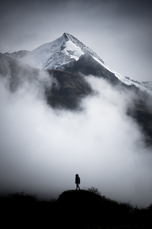 A man standing before a snow covered mountain