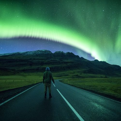 Man watching the aurora above the roads and mountain