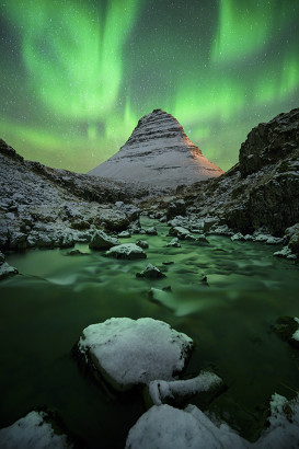 The Northern Lights above a snow covered mountain and river