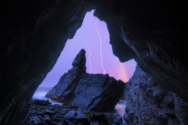 Lightning and rainbow outside a cave