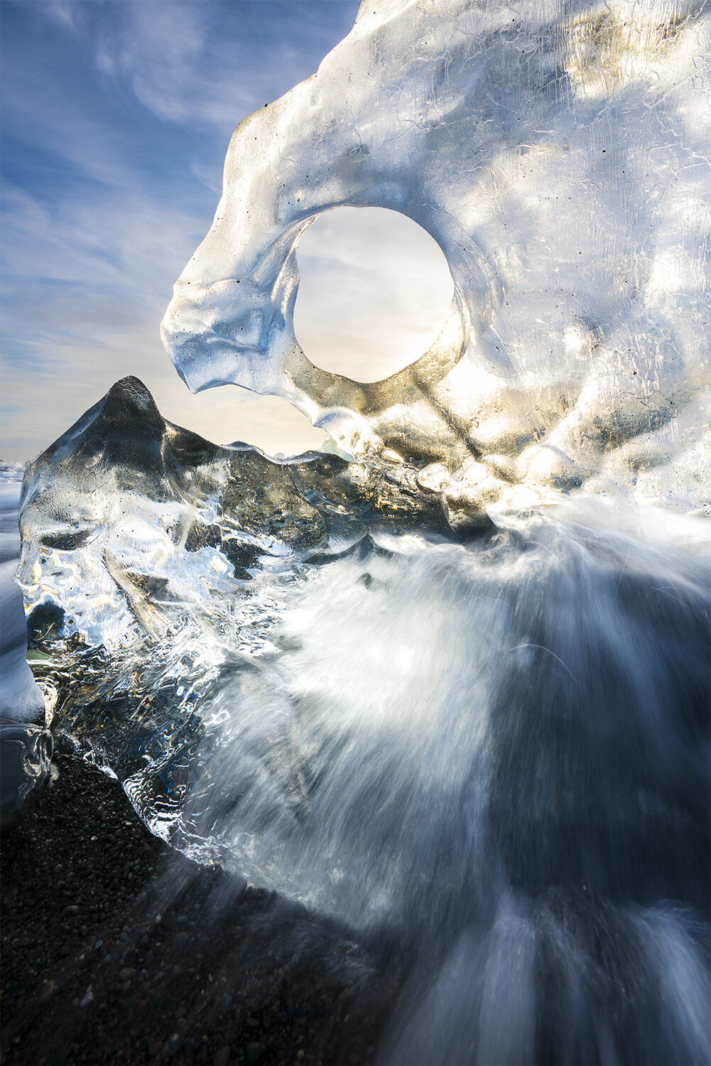 Water rushing over ice upon a beach.
