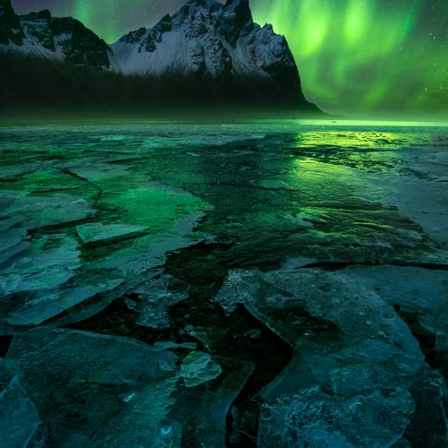 Frozen ice and the aurora over Vesturhorn in Iceland