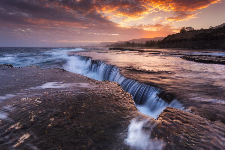 Rock shelf waterfall at sunset.