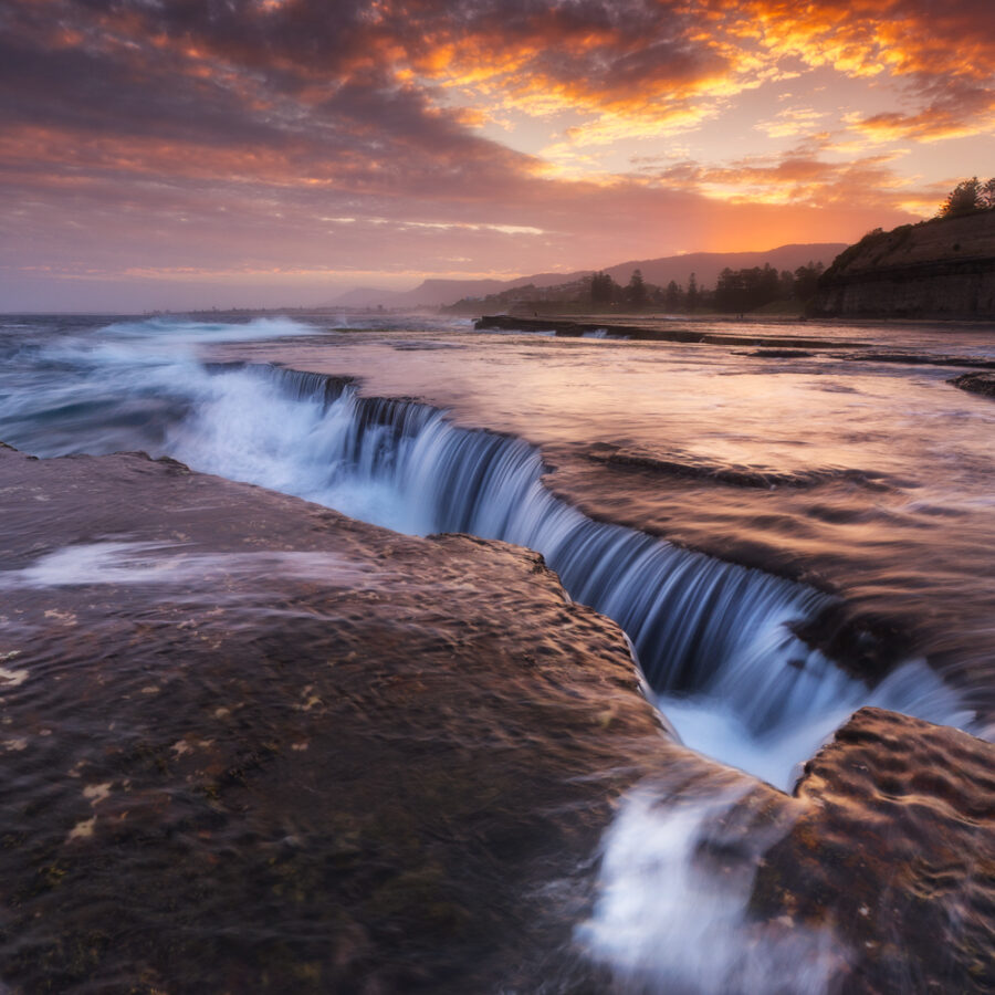 Rock shelf waterfall at sunset.