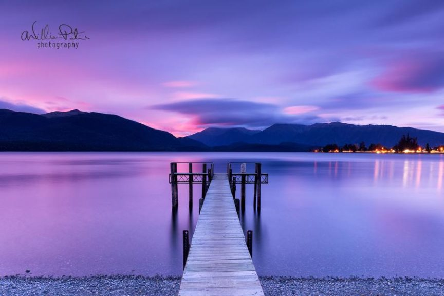 A vilet sunset upon a lake with a pier.