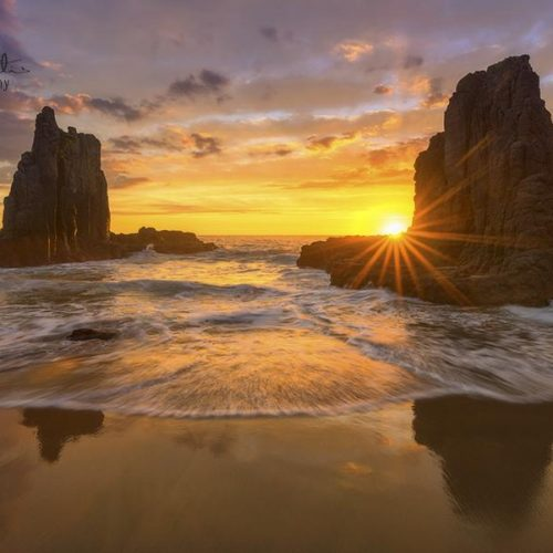 Australian sunrise over the ocean with large rock formations.