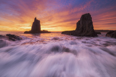 Large rocks by the ocean at sunrise.