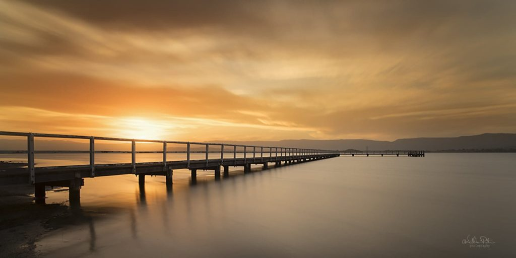Sunset over a pier on a lake.