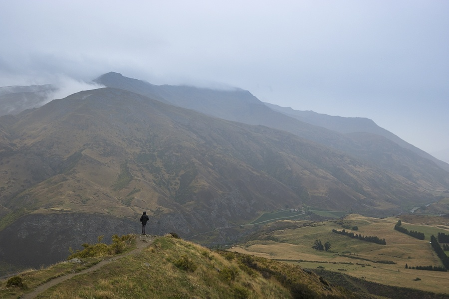 A man standing in a vast, mountainous landscape.