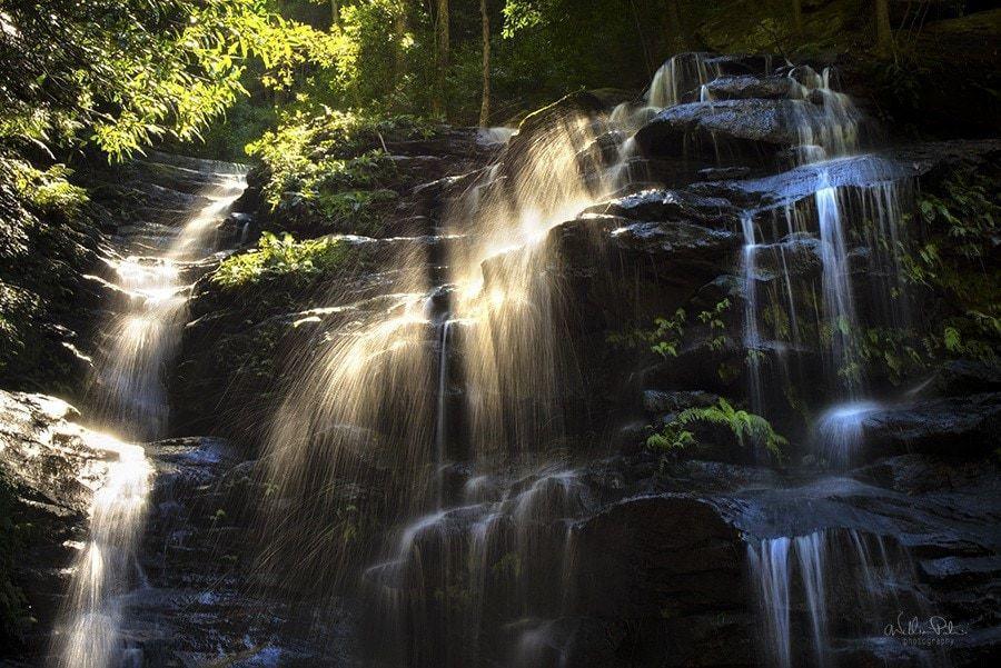 Sunlight beaming through a waterfall.
