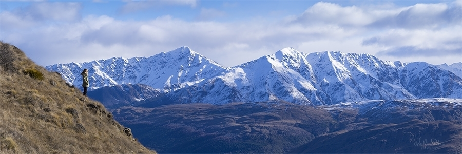 A woman standing in front of New Zealand mountains.