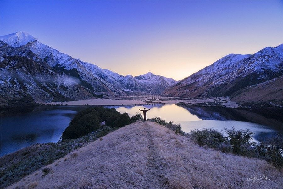 A man standing before a lake and snow covered mountains in New Zealand.