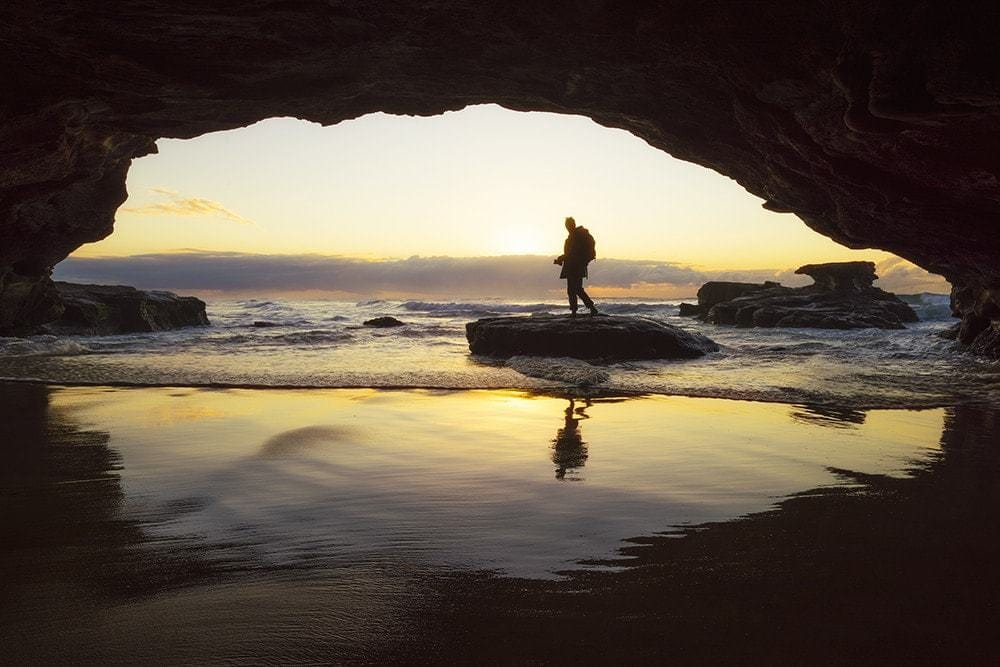 A man inside a sea cave at sunrise.