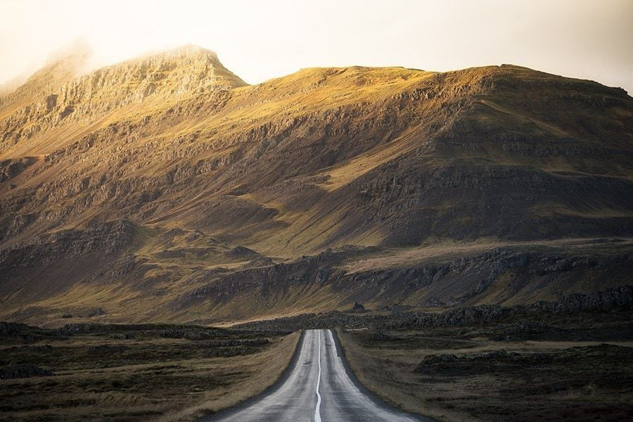 A road leading to sun lit mountains