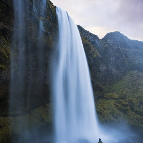 A man standing under a large waterfall