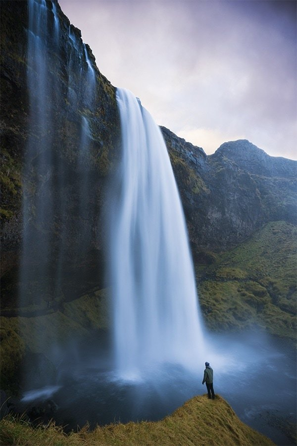 A man standing underneath a large waterfall in Iceland